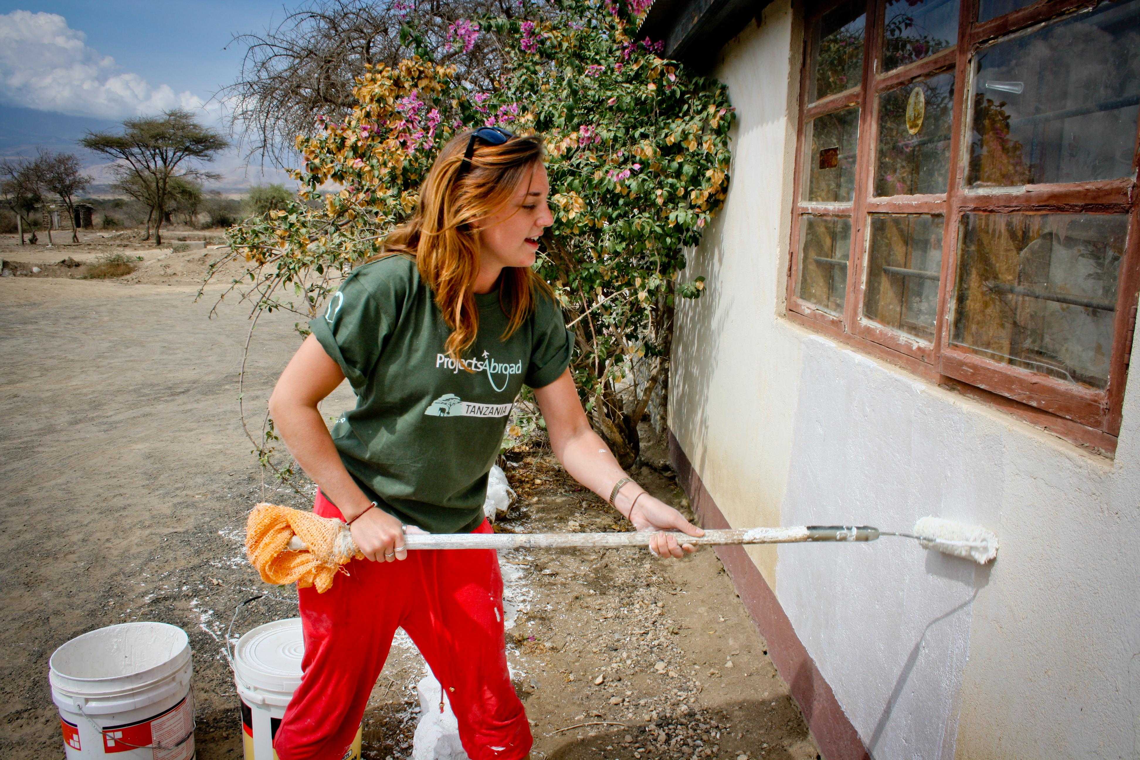 A teenage volunteer doing construction work in Tanzania paints a wall white.